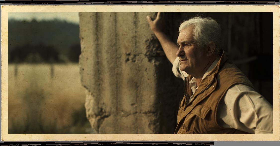 Pierre Seillan leaning against stone barn at Anakota estate